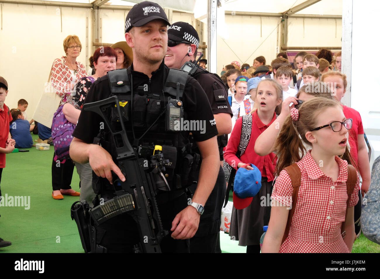 Armed Police officers among visiting school children at the Hay Festival May 2017 - Stock Image