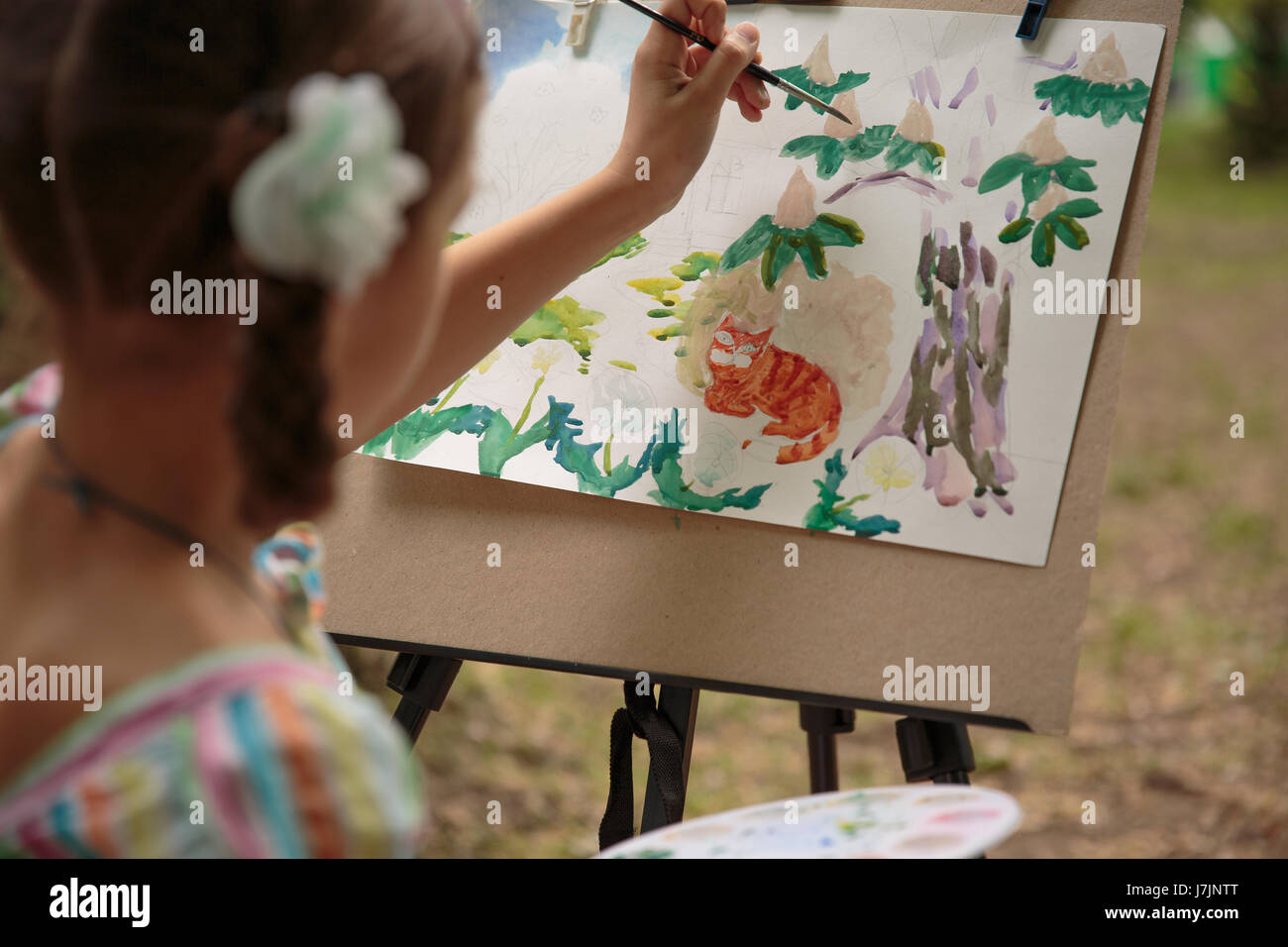 girl paints on an easel in the drawing lesson. Girls Hand draws a pencil tree trunk on a white sheet. Drawing lesson - Stock Image