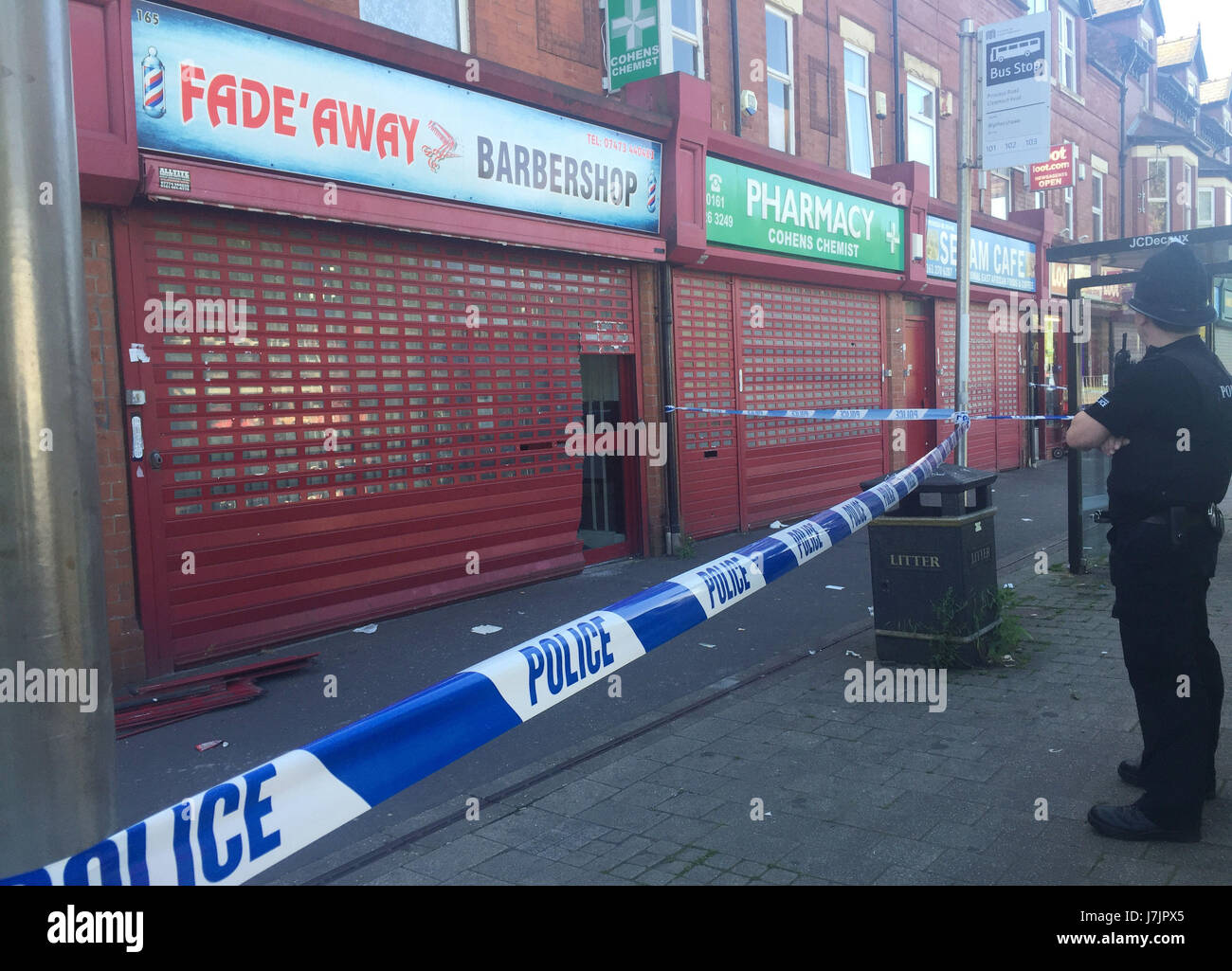 A police cordon outside the Fade Away barbershop in Princess Road in Moss Side, Manchester. Counter-terror police - Stock Image