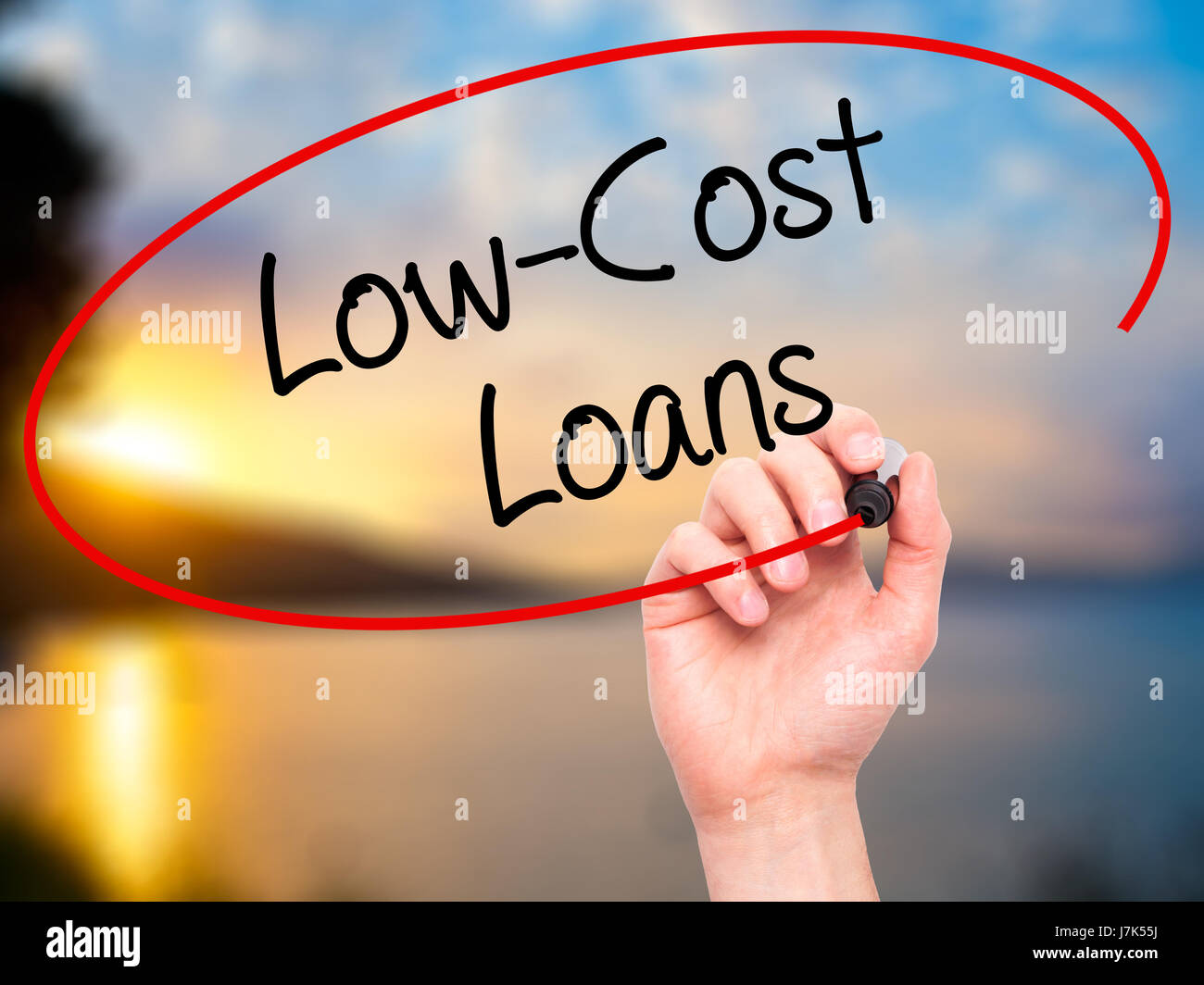 Man Hand writing Low-Cost Loans with black marker on visual screen. Isolated on background. Business, technology, Stock Photo