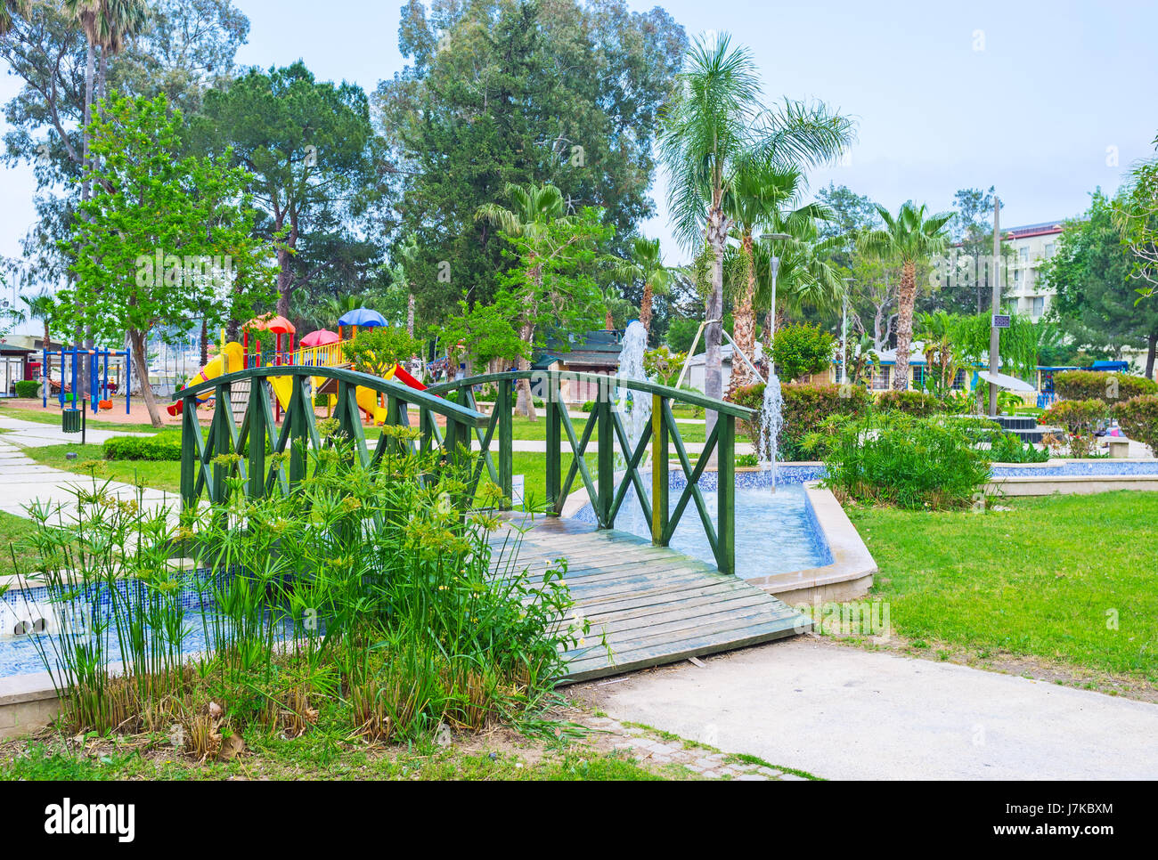 The small wooden bridge over the pond with fountains in Olbia park of Kemer resort, Turkey. - Stock Image