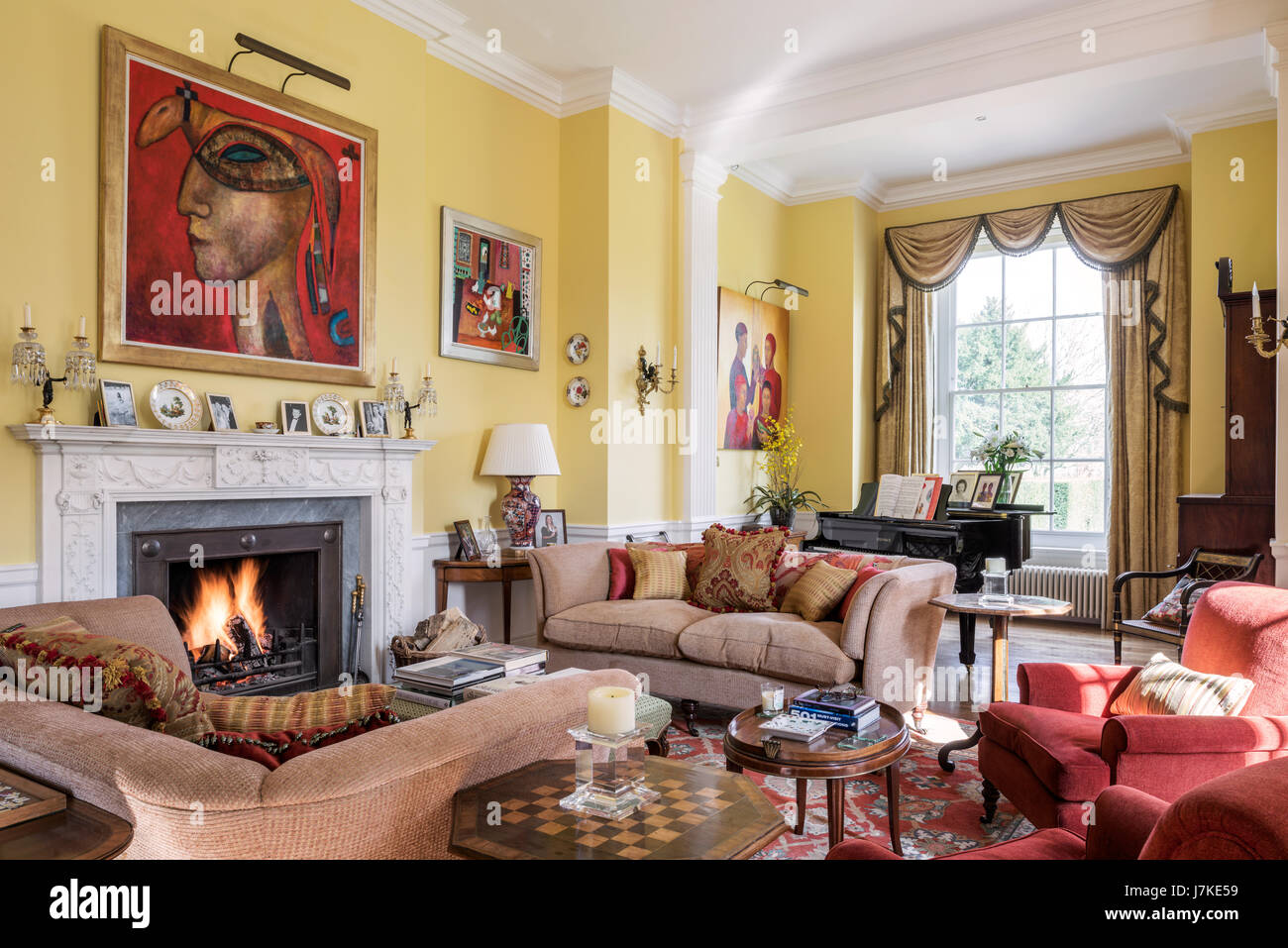 Mixed modern art and antique furniture in large yellow drawing room