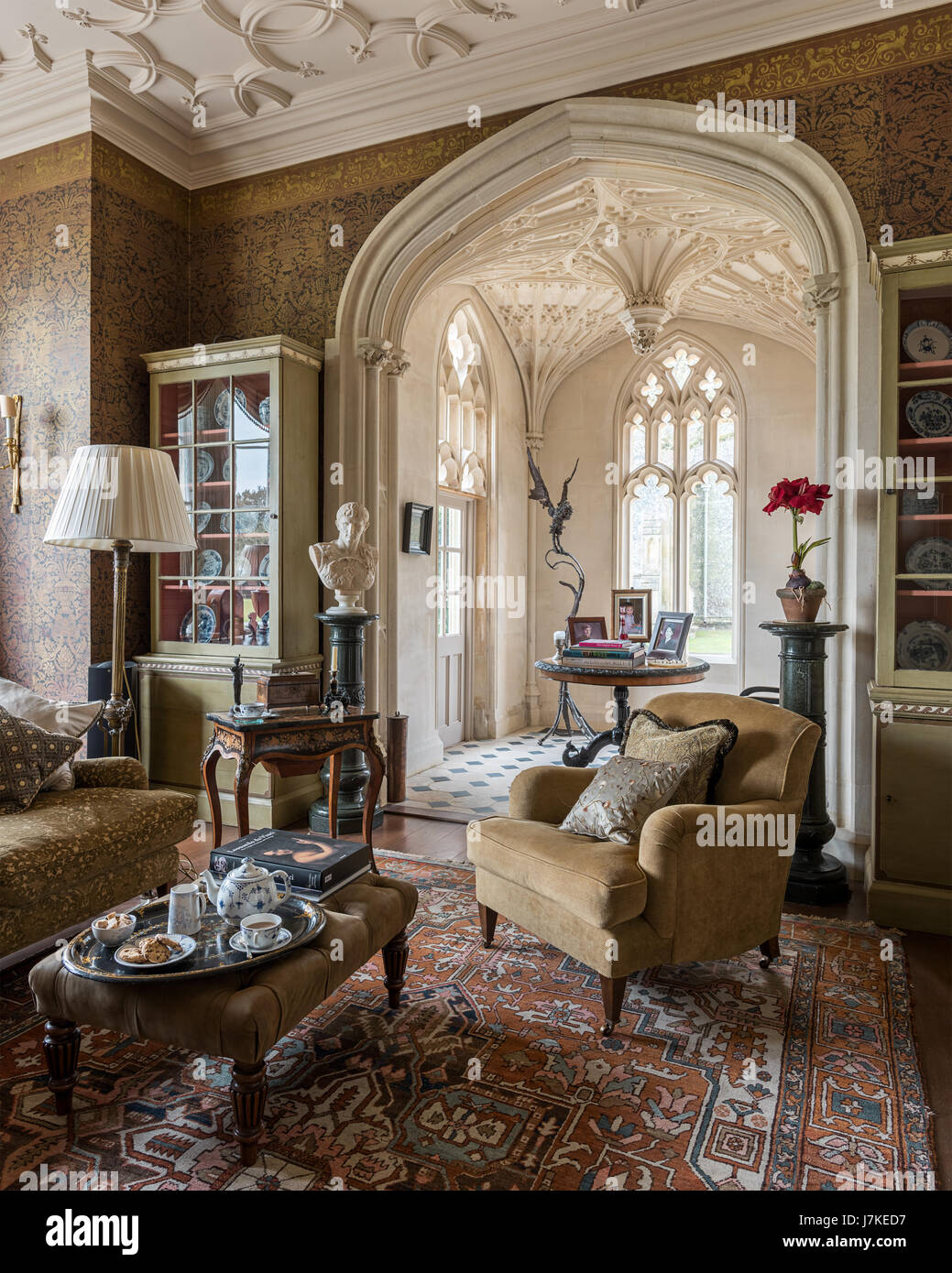 Patterned wallpaper by Zuber in library with antique persian rug and Gothic windows. The sofa