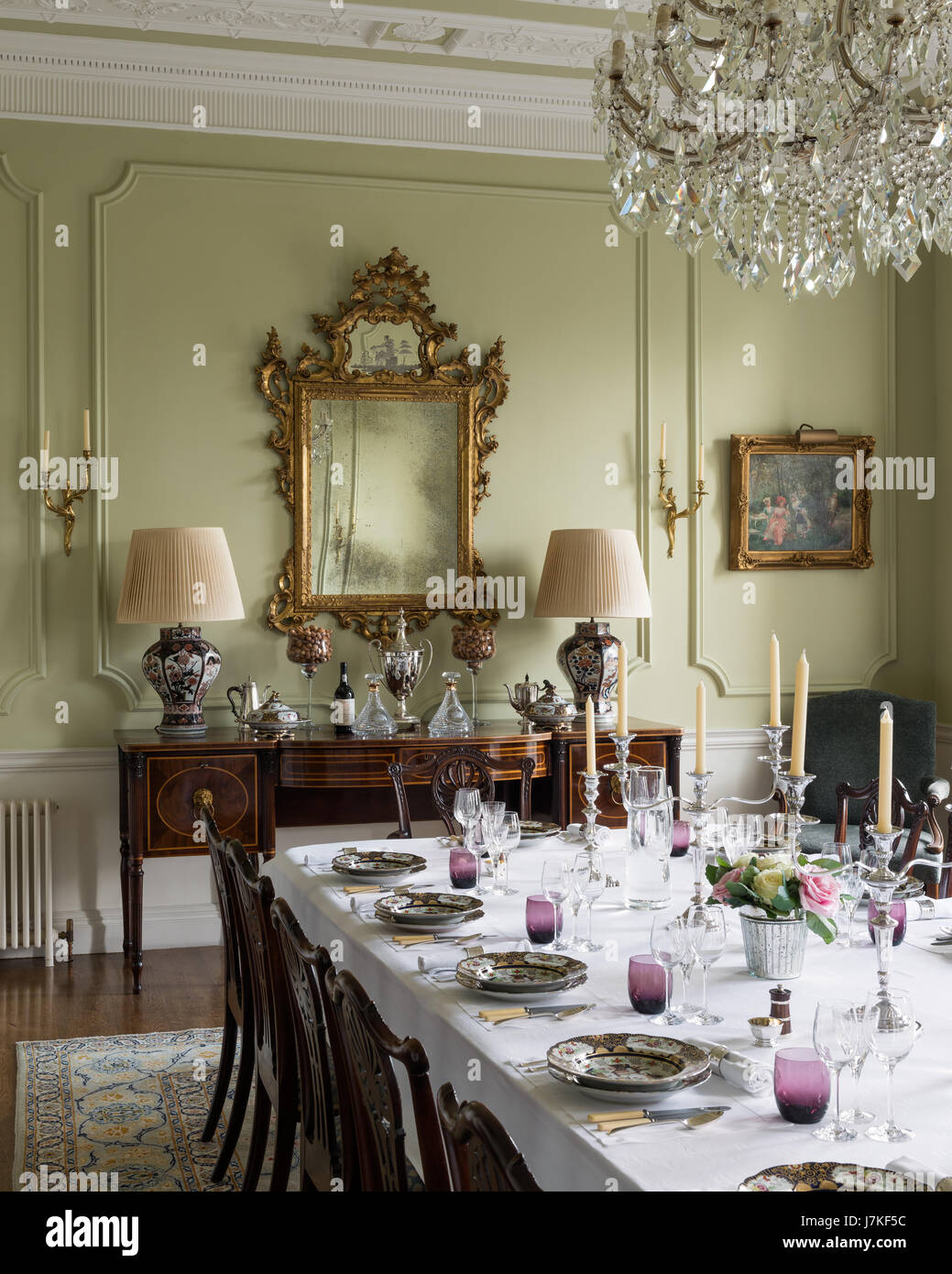 Georgian style dining chairs in grand dining room with glass chandelier and  antique sideboard. - Georgian Style Dining Chairs In Grand Dining Room With Glass Stock