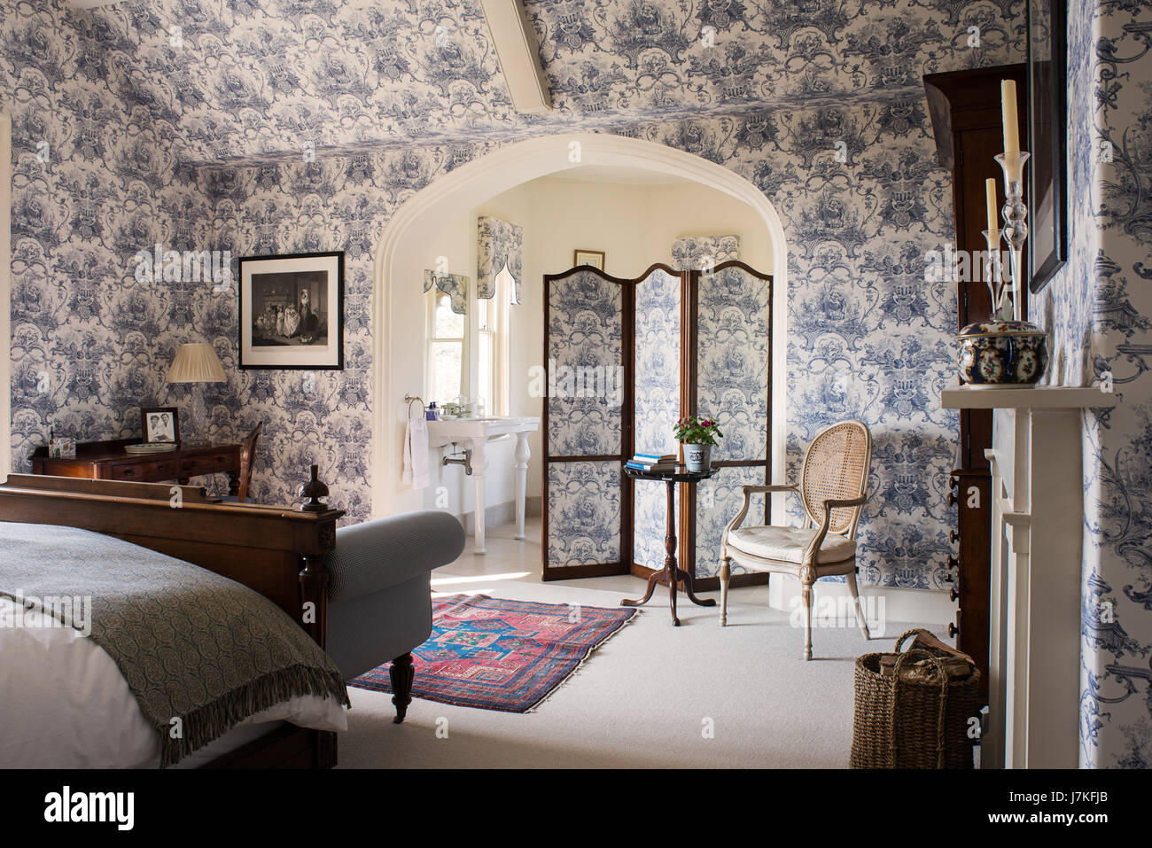 Large ensuite bedroom with toile de jouy wallpaper and matching folding screen. Stock Photo
