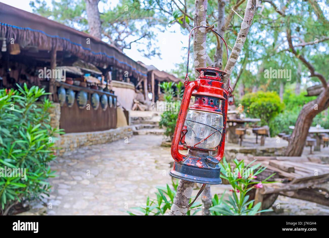 The vintage kerosene lamp decorates the rustic outdoor cafe in Yoruk park, Kemer, Turkey. - Stock Image