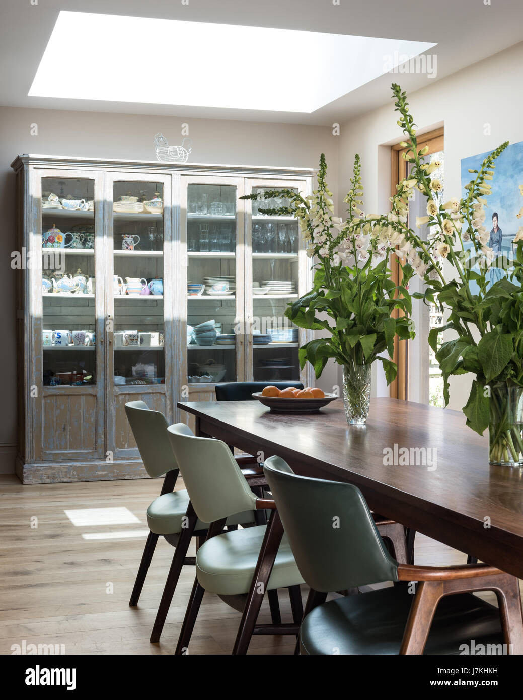 Salvaged Iroko table in dining room with leather chairs and large ...