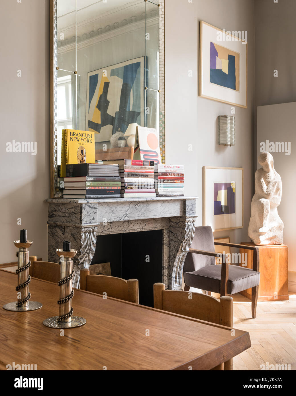 French grey marble fireplace with leaf motif and simple 1940s style mirror - Stock Image