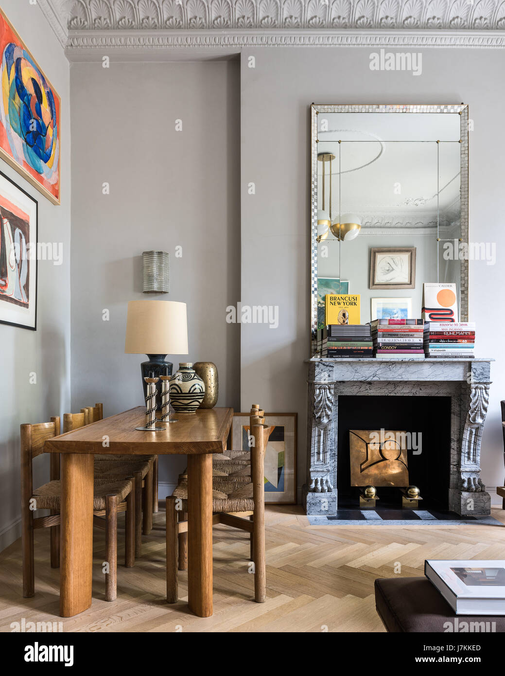 Wooden dining table and chairs by Charlotte Perriand with 1940s mirror above French grey marble fireplace - Stock Image