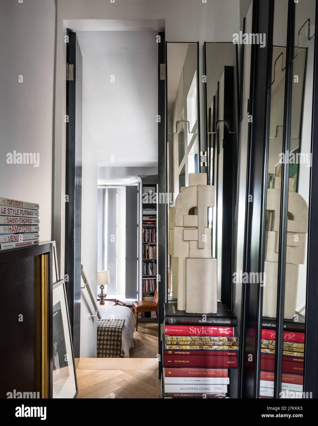 Books stacked at doorway to split-level bedroom - Stock Image