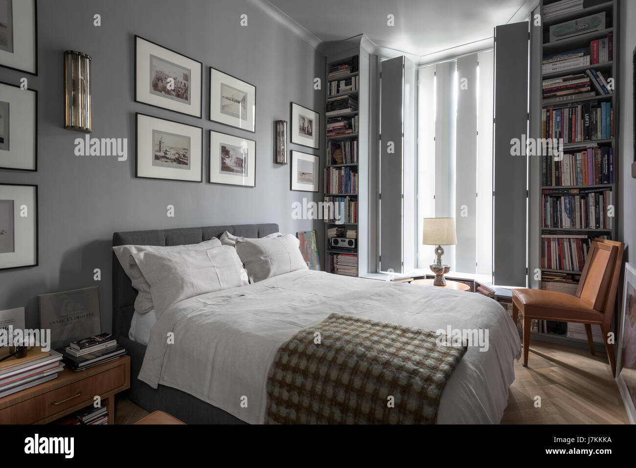 Calm grey tones and book shelving in bedroom with 1940s Murano glass wall lights - Stock Image