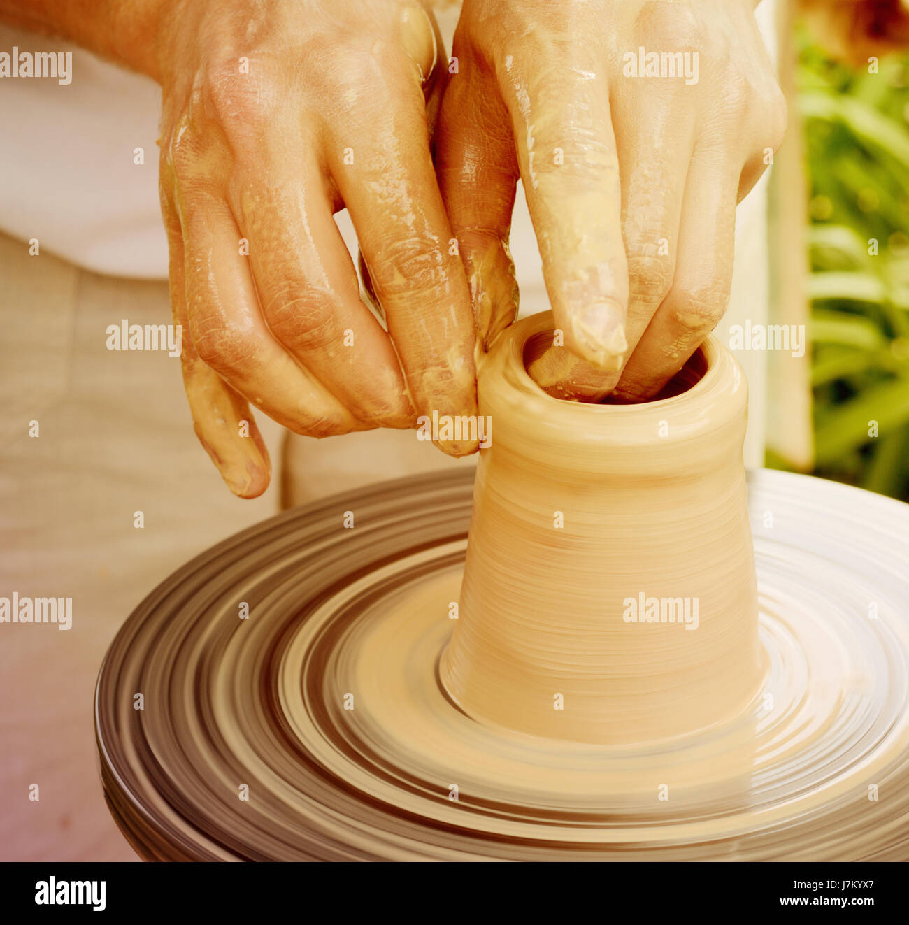 Male potter makes vessel with pottery wheel. - Stock Image