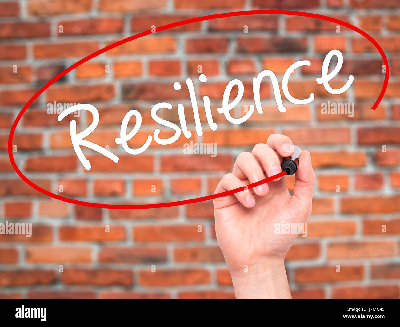 Man Hand writing Resilience with black marker on visual screen. Isolated on bricks. Business, technology, internet - Stock Image