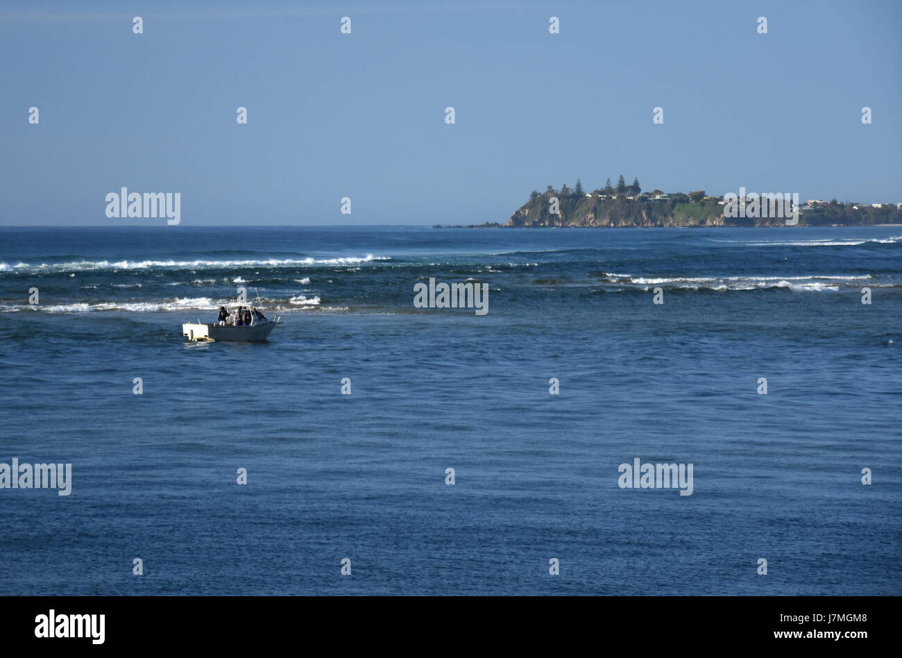 Fishing boat with people on the sea at Tuross Head. Potato Point in the background. Tuross Head is a seaside village - Stock Image