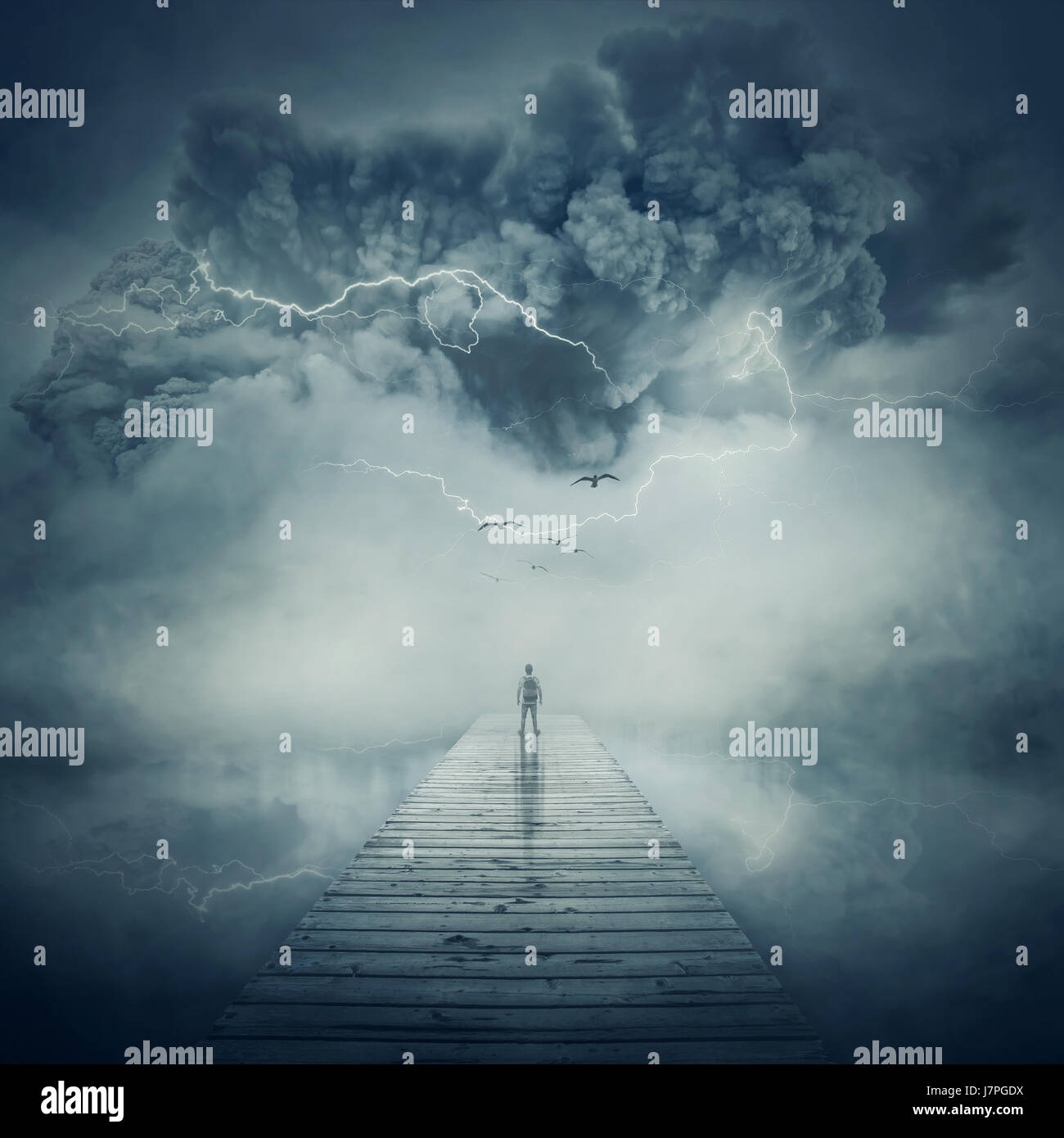 Fantastic view as a man, stand on the wooden pier at the middle of the lake in a foggy and stormy day watching a - Stock Image