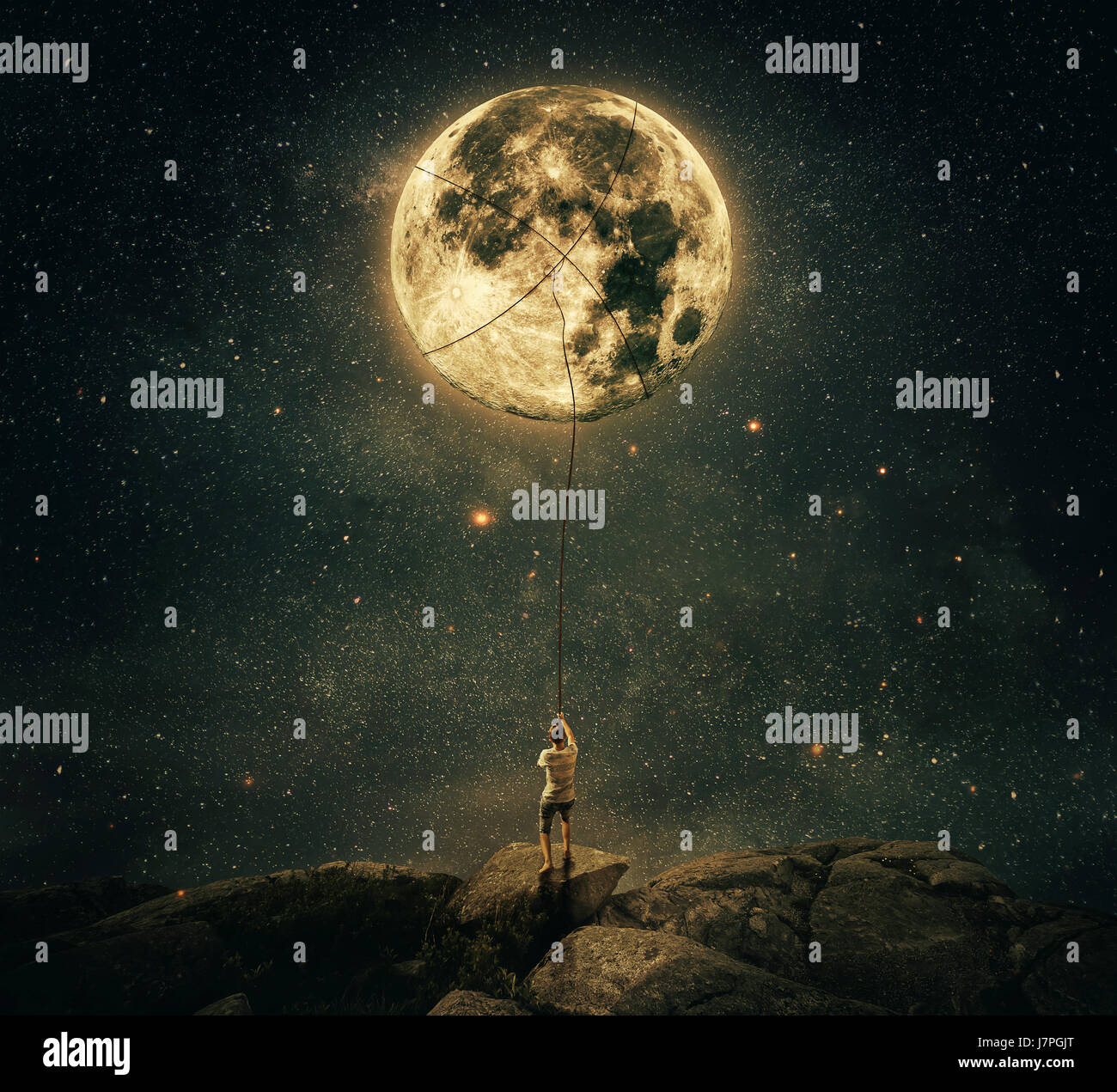 Imaginary view as a young man, holding a rope, try to catch and pull the full moon from the night sky. Achievement - Stock Image