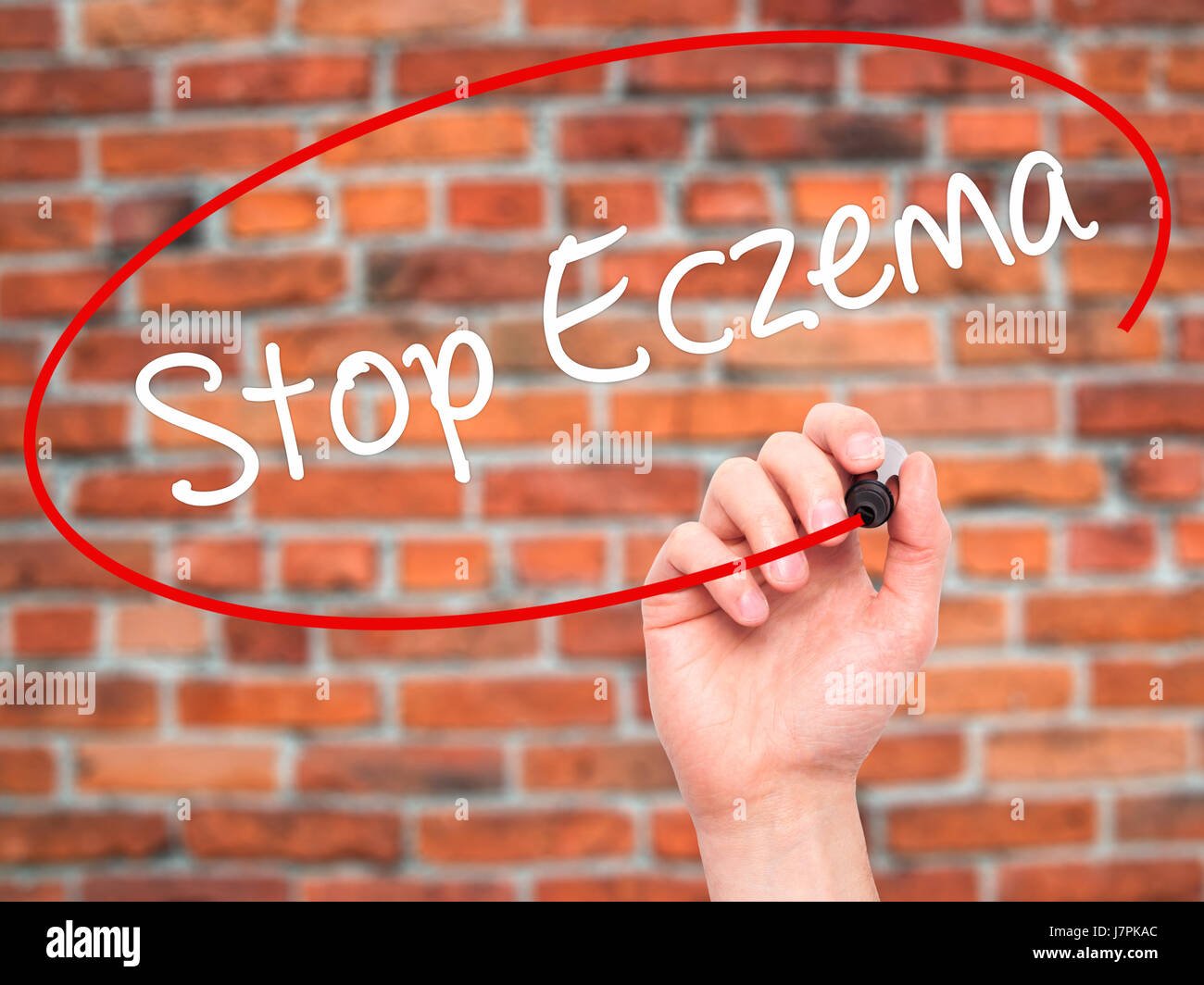 Man Hand writing Stop Eczema with black marker on visual screen. Isolated on bricks. Business, technology, internet Stock Photo