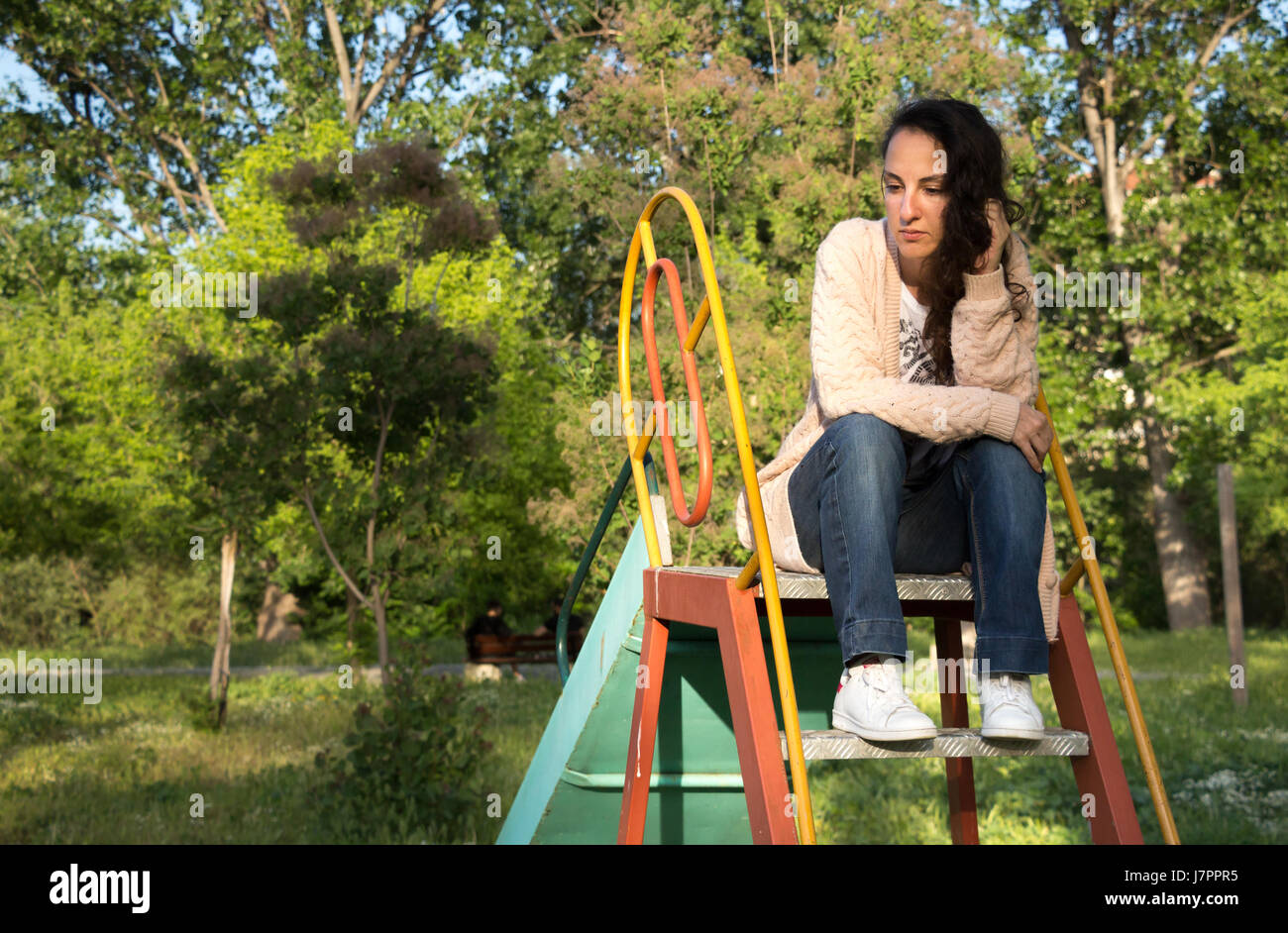 Portrait of a young woman looking away sitting on the top of a slide at a park, thinking, remembering. - Stock Image