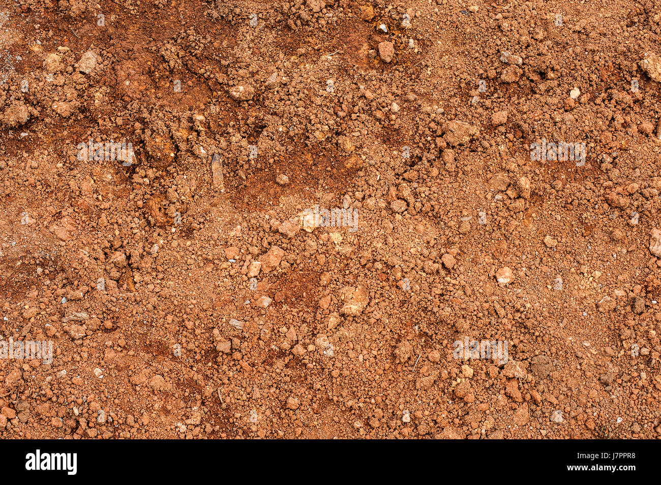 Tropical laterite soil or red earth background. Red mars seamless sand background. Top view - Stock Image