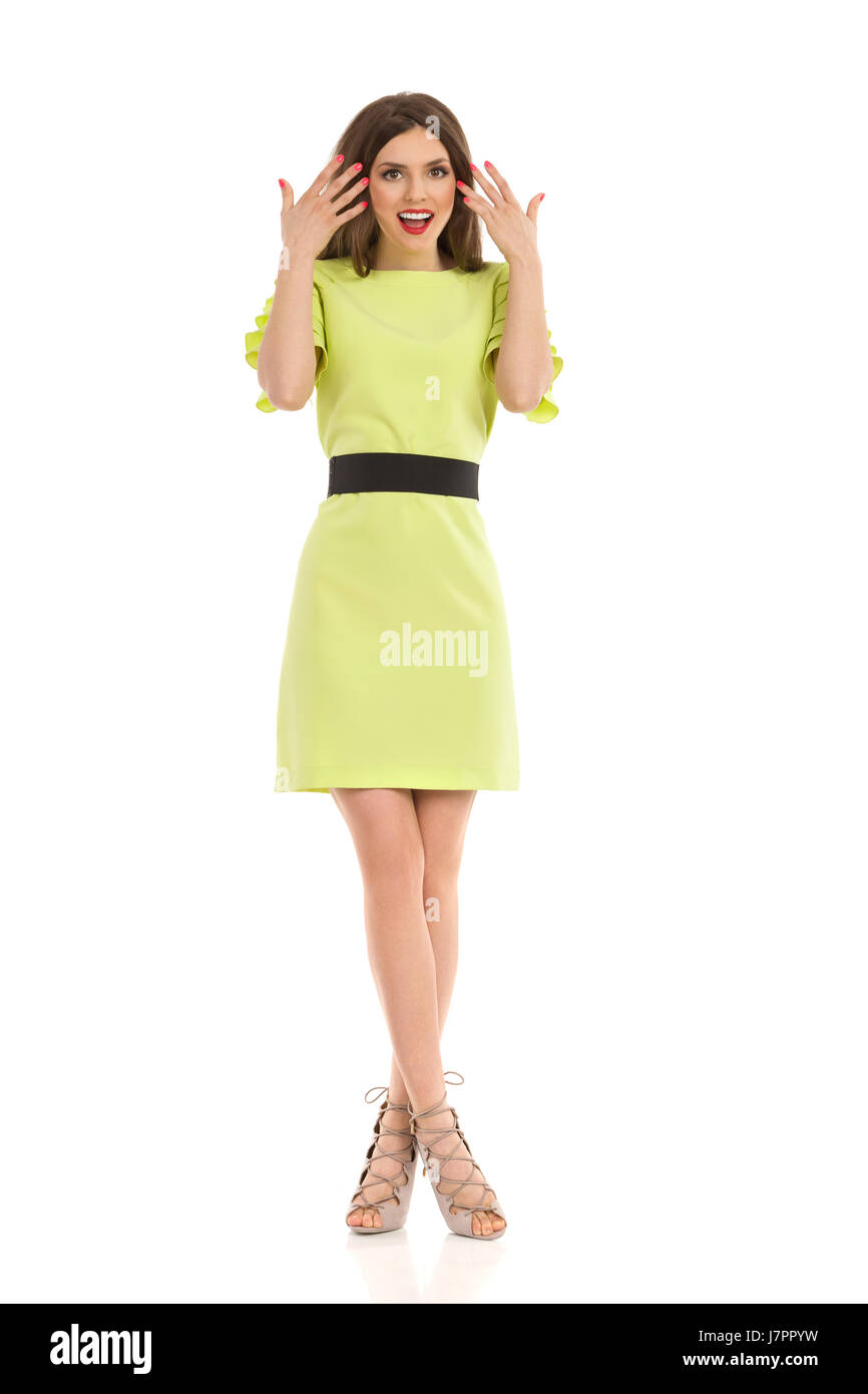 Surprised beautiful woman in lime green dress, beige high heels and black belt standing with legs crossed and looking - Stock Image