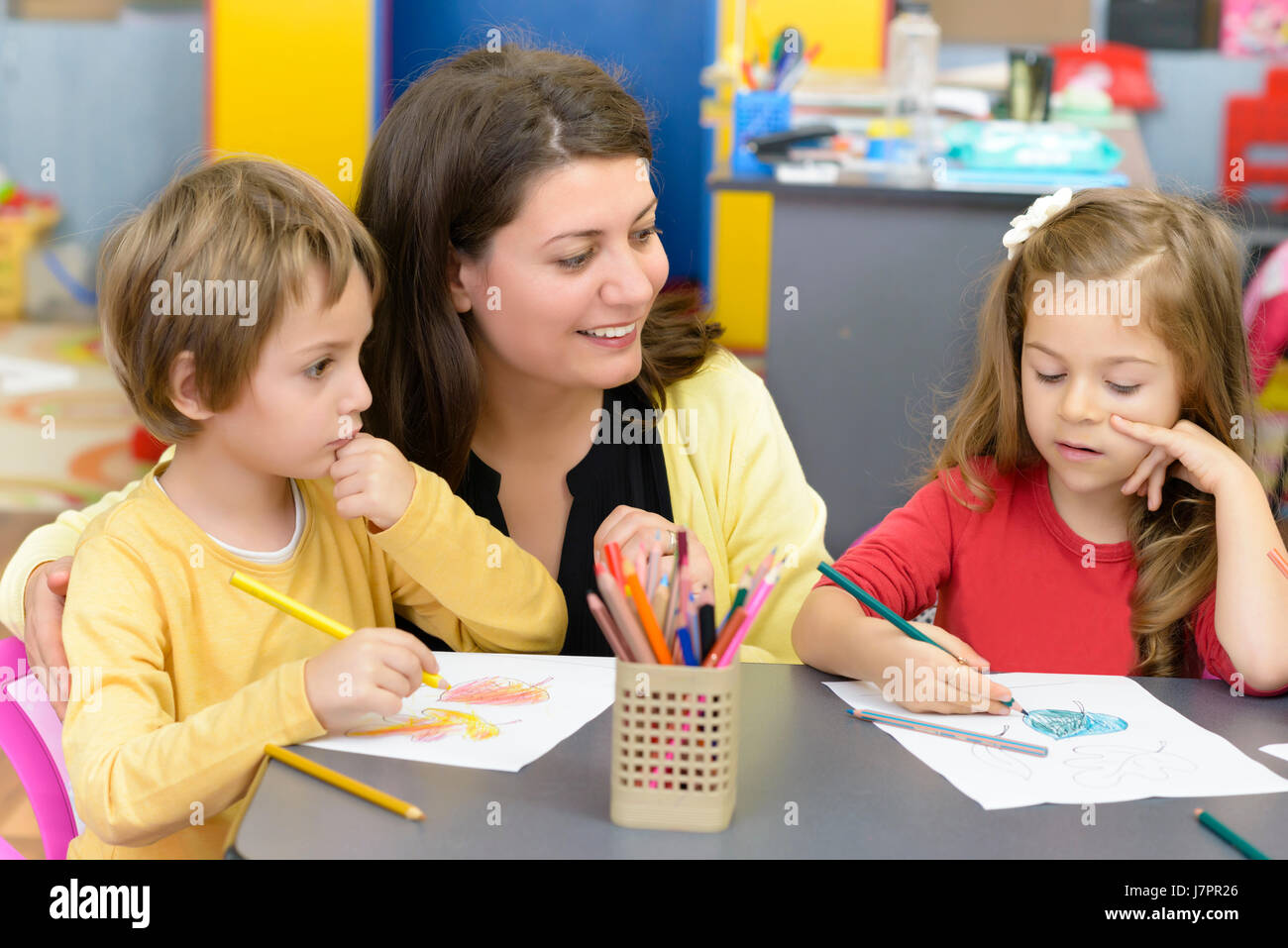 Kids drawing at kindergarten being supervised by educator - Stock Image