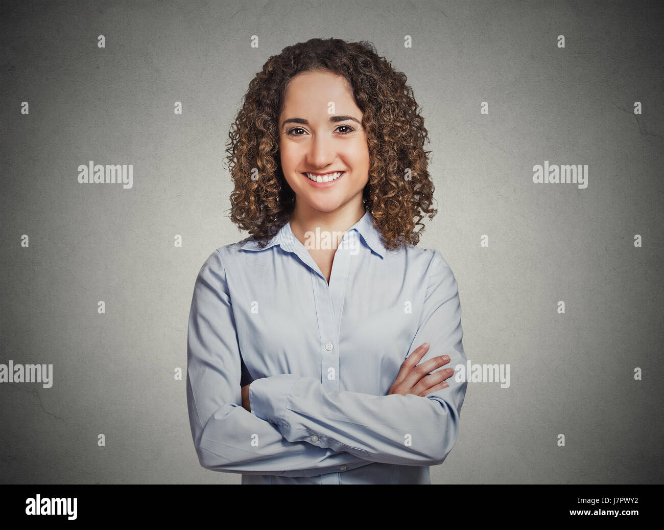 Closeup portrait, happy, confident, successful young professional woman in blue shirt with arms crossed folded isolated - Stock Image