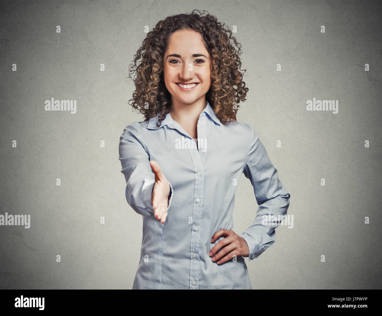 Closeup portrait, young, curly, brown hair, smiling woman, student, customer service agent giving you handshake - Stock Image