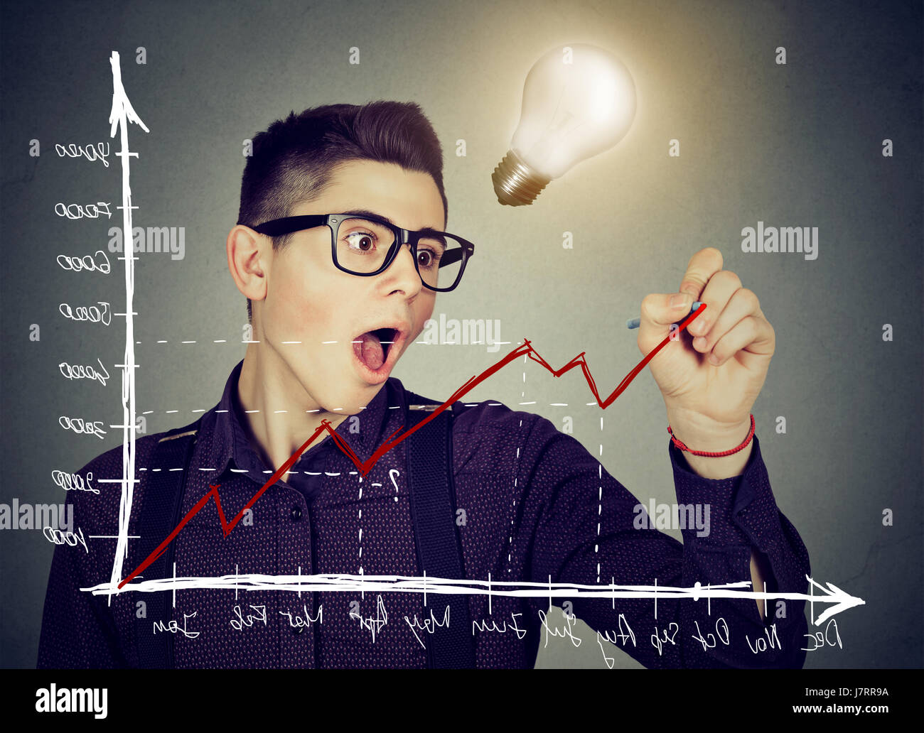 Young business man charting a positive trend graph has bright idea - Stock Image