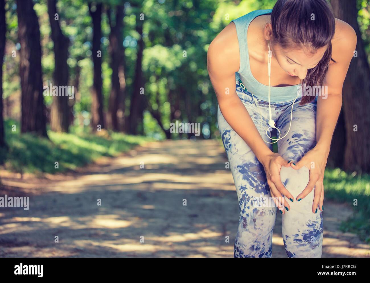 Female athlete runner touching knee in pain, fitness woman running in summer park. - Stock Image