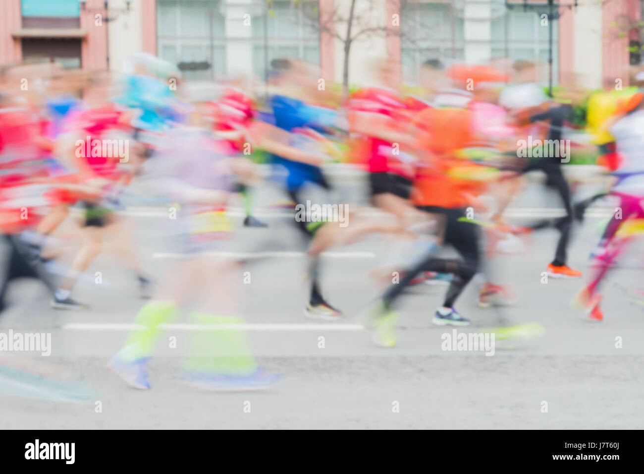 Abstract background of colored group of running athletes on street, city marathon, blur effect, unrecognizable faces. - Stock Image