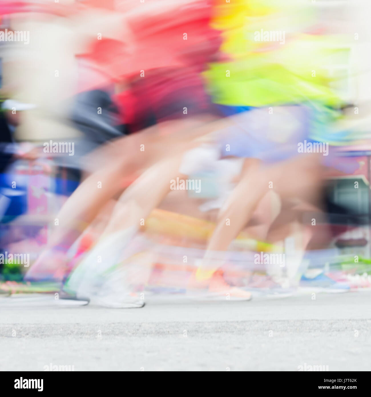 Abstract blurred sport background of colorful running feet and legs of runners during marathon on city streets. - Stock Image