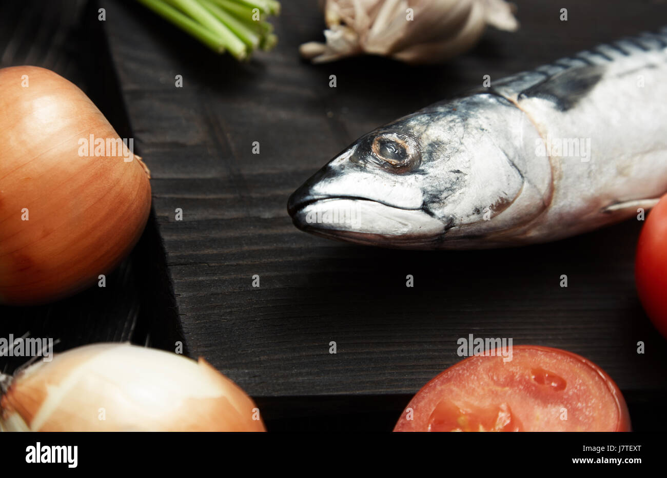 Mackerel and vegetables on a wooden table. Horizonal photo - Stock Image