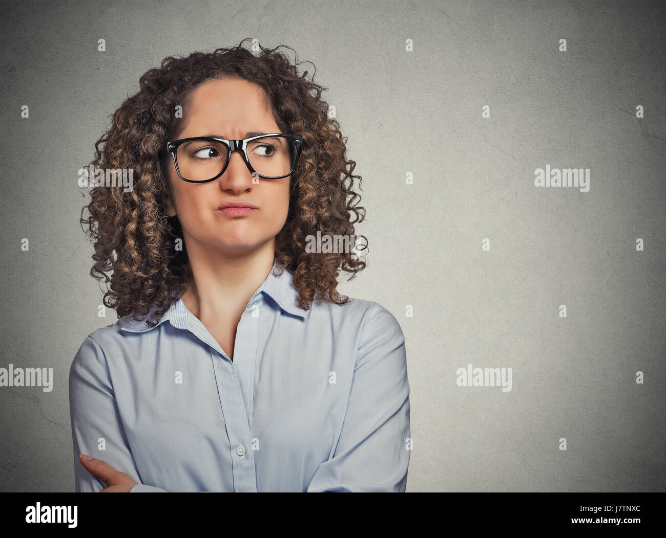 Displeased suspicious young woman with glasses looking sideways isolated on grey wall background. Negative face - Stock Image