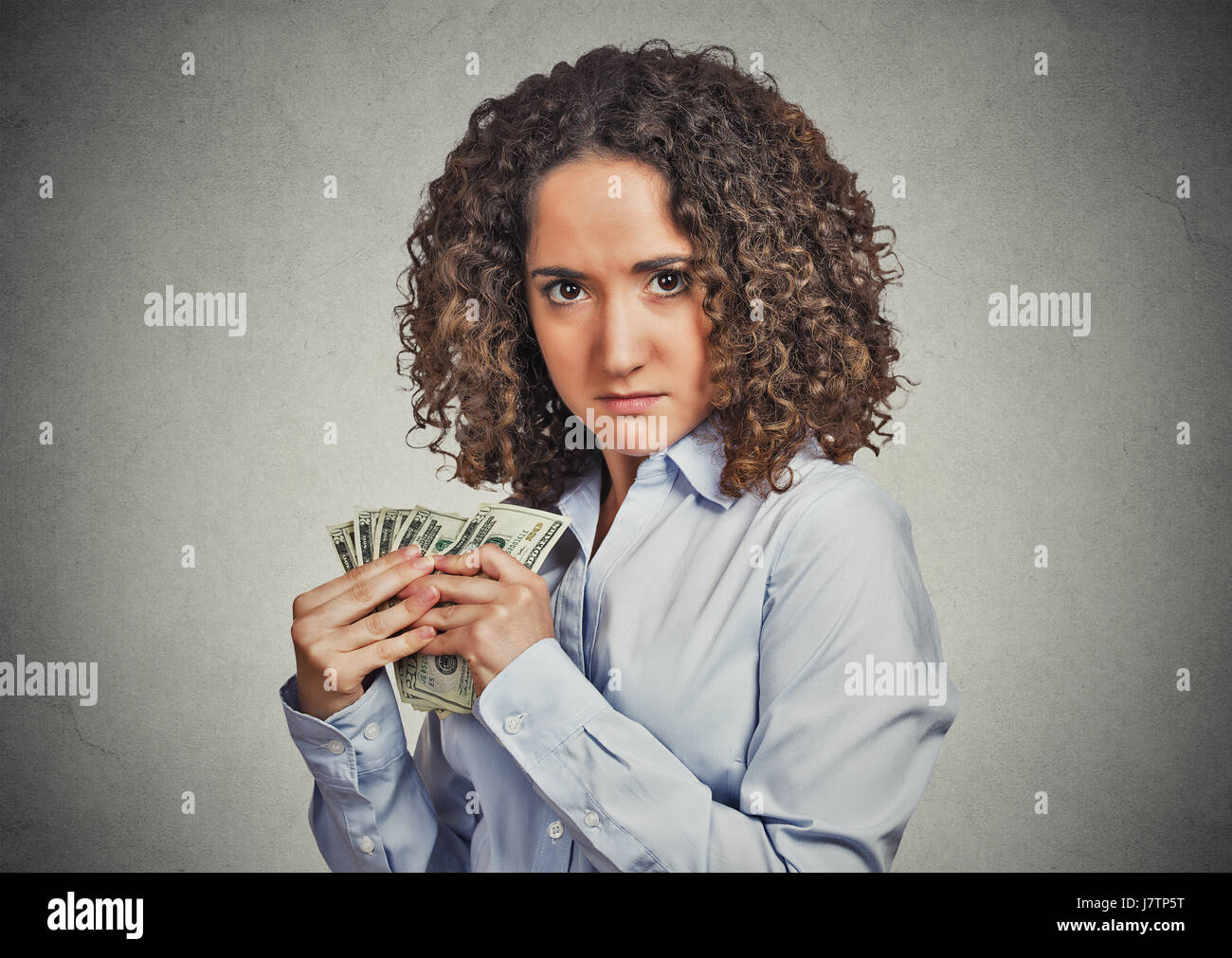 Closeup portrait greedy young woman corporate business employee, worker, student holding dollar banknotes tightly - Stock Image