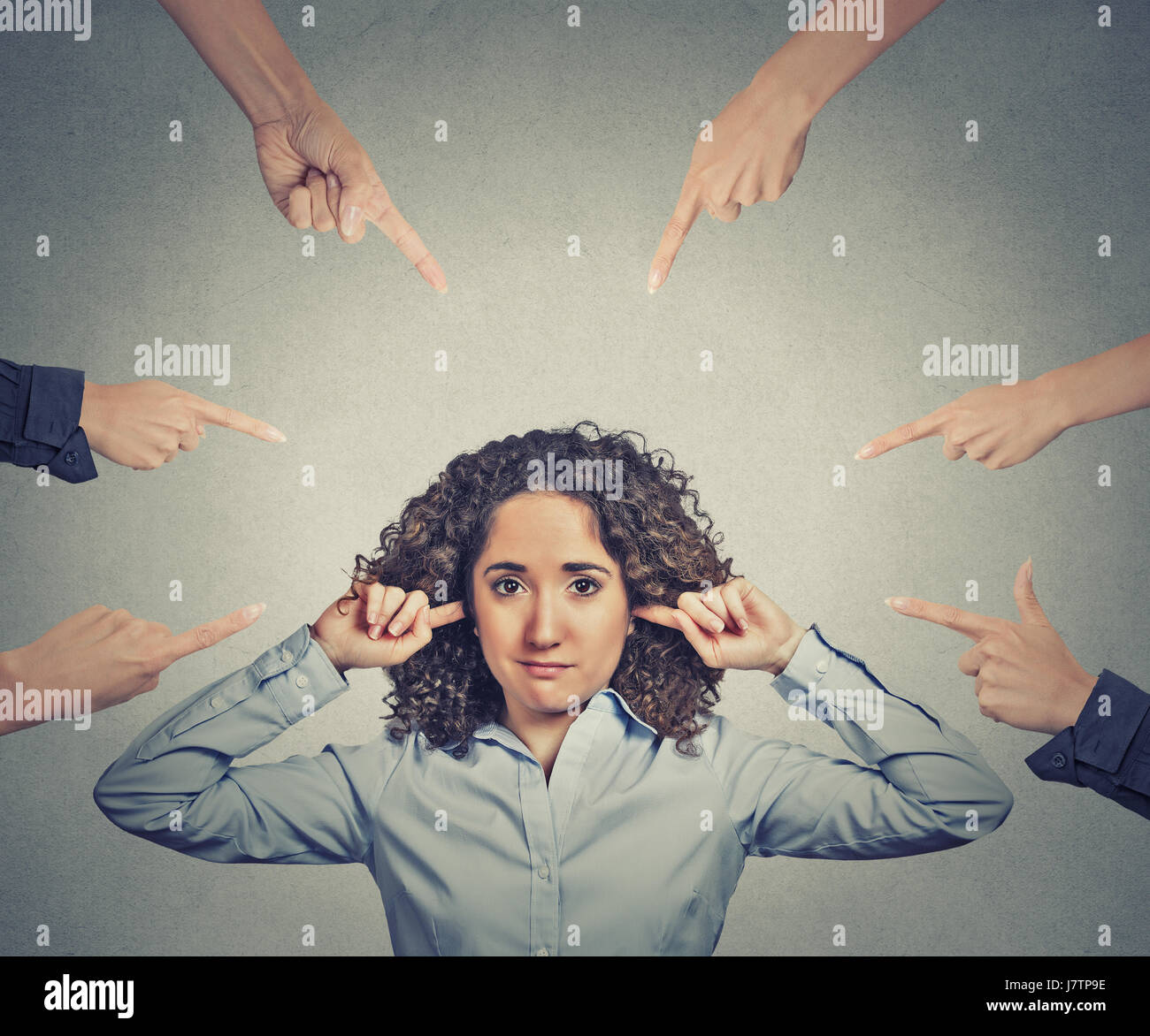 Concept of accusation of guilty businesswoman. Portrait unhappy sad upset woman plugging her ears many fingers pointing - Stock Image