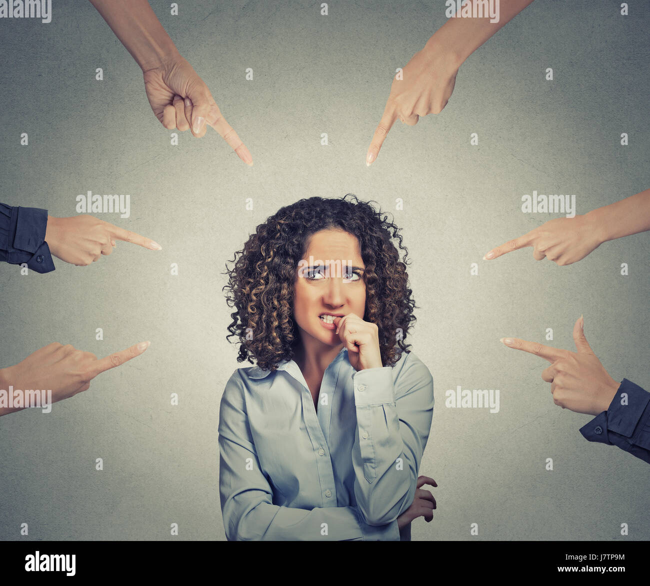 Concept of social accusation of guilty businesswoman many fingers pointing at isolated on grey office wall background. - Stock Image