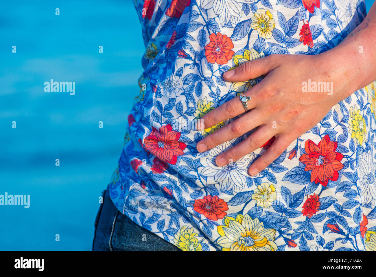 Young lady's hand laid flat on flowery t-shirt stomach tummy belly - concept of stomach ache, pain - Stock Image