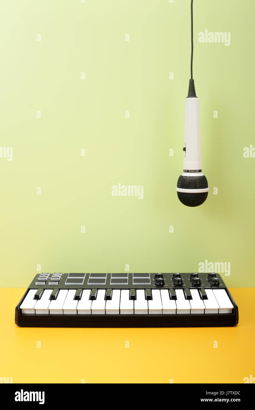 Musical instrument - MIDI keyboard and vokal microphone for a karaoke hangs down on top on a flavovirent background. - Stock Image