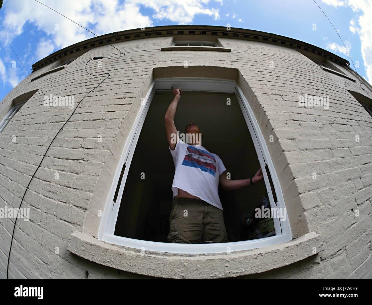 man refurbishing a sash window in an old house - Stock Image