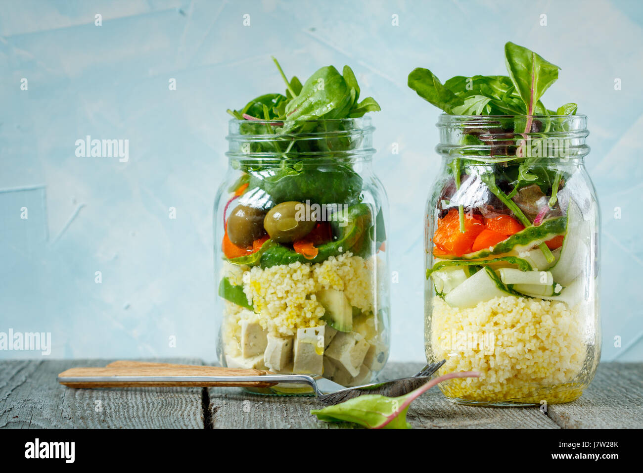 Colorful salad with couscous, tofu and vegetables in a jar. Love for a healthy vegan food concept - Stock Image