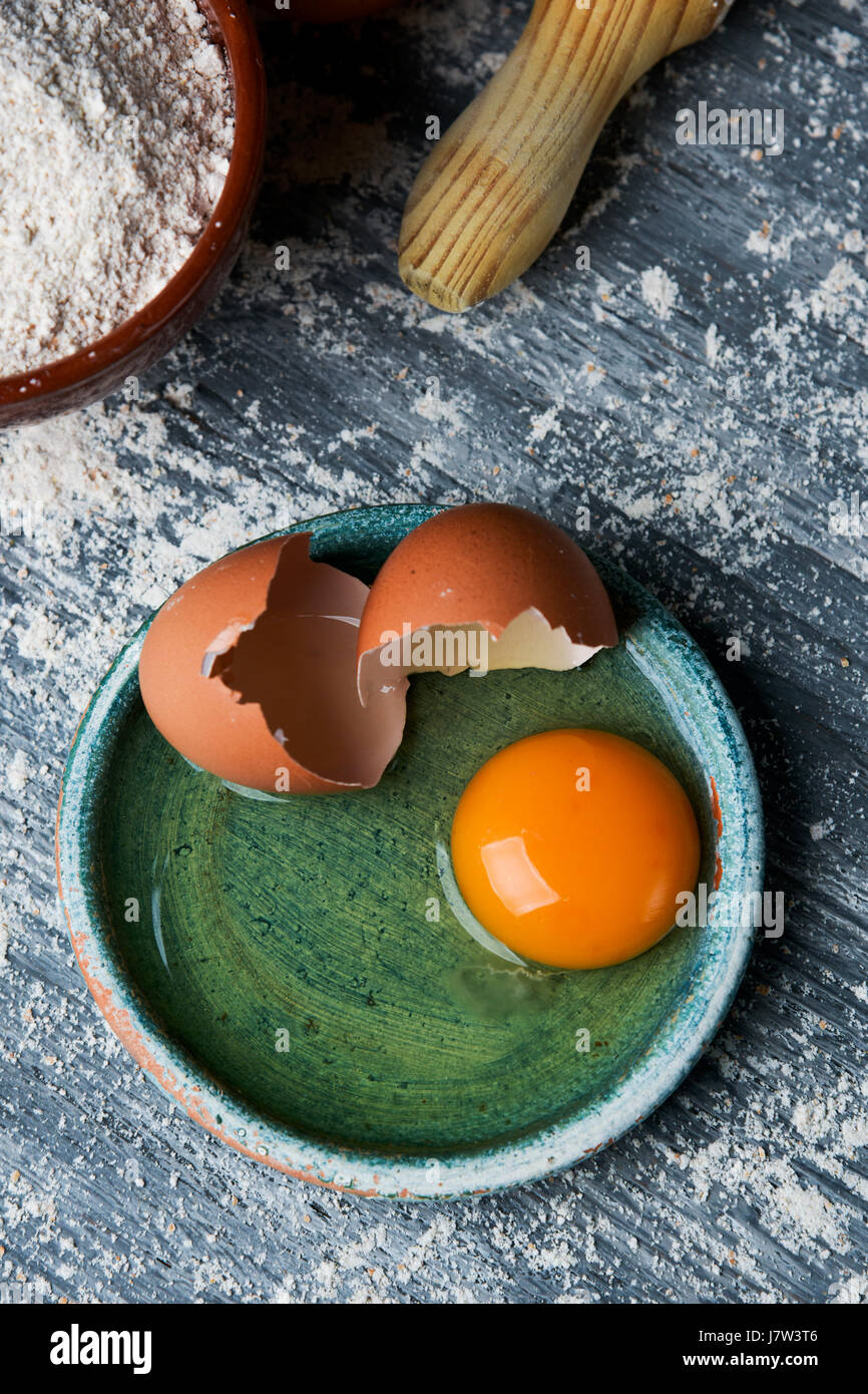 high-angle shot of a cracked egg in a green plate, an earthenware bowl with flour and a wooden rolling pin on a - Stock Image