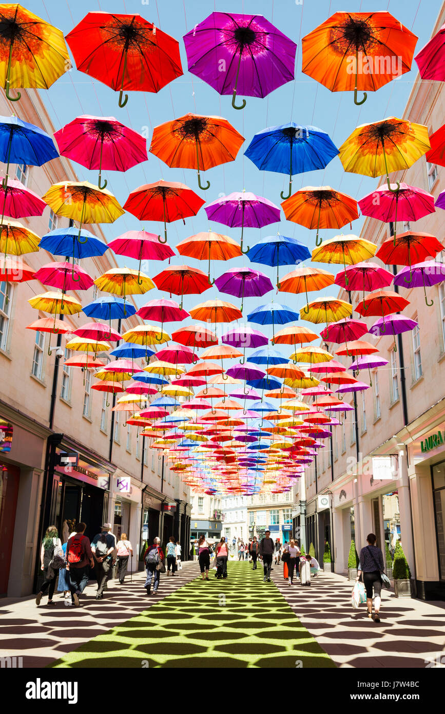 Bath, Somerset, UK. Colourful umbrellas suspended above the street as part of an art festival. - Stock Image