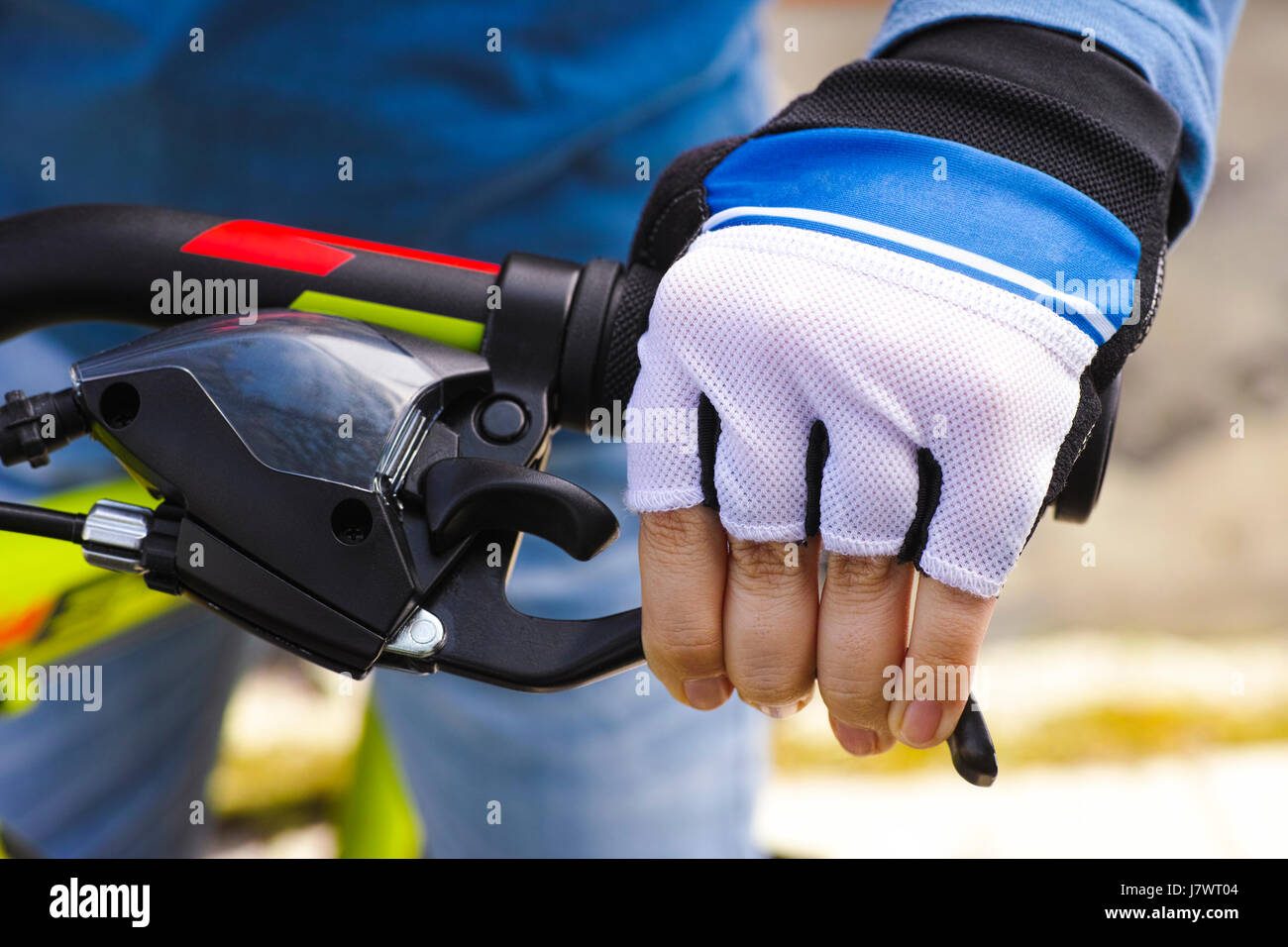 Child hand with glove on handlebars with brake lever. Close-up. - Stock Image
