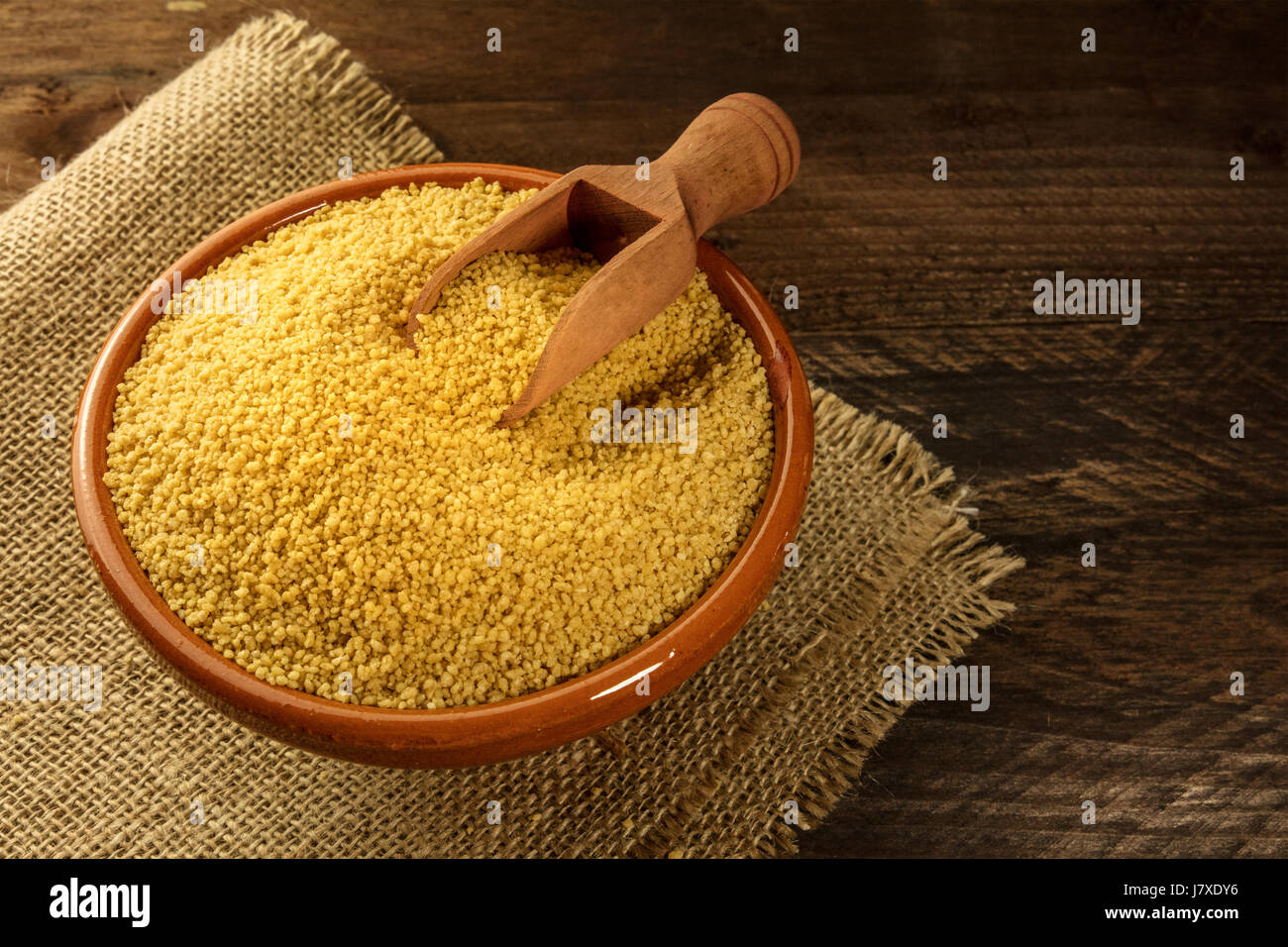 Bowl of couscous on rustic textures with copyspace - Stock Image