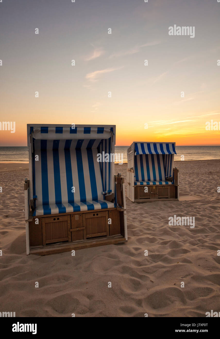 Two beach chairs at North Sea beach of Hornum, Sylt, in sunset Stock Photo