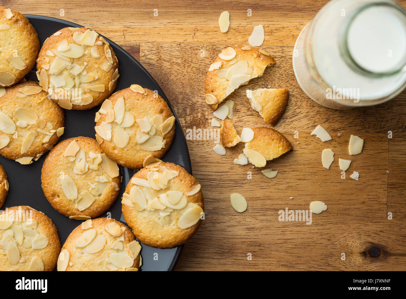 Sweet almond cookies with milk on wooden table. Top view. - Stock Image