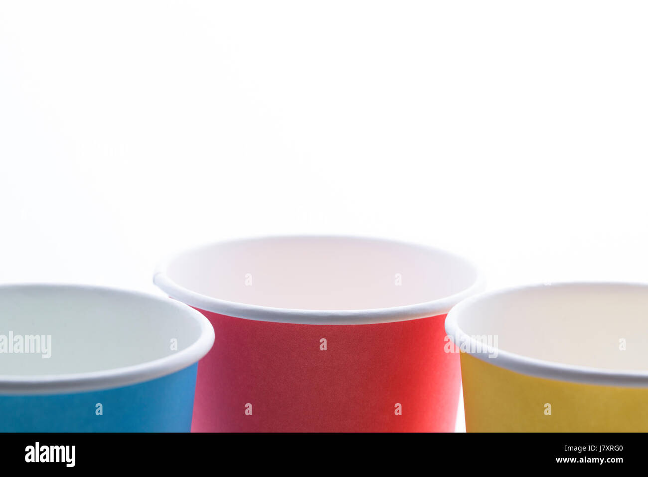 Yellow, blue and orange disposable cups isolated on white background. Stock Photo