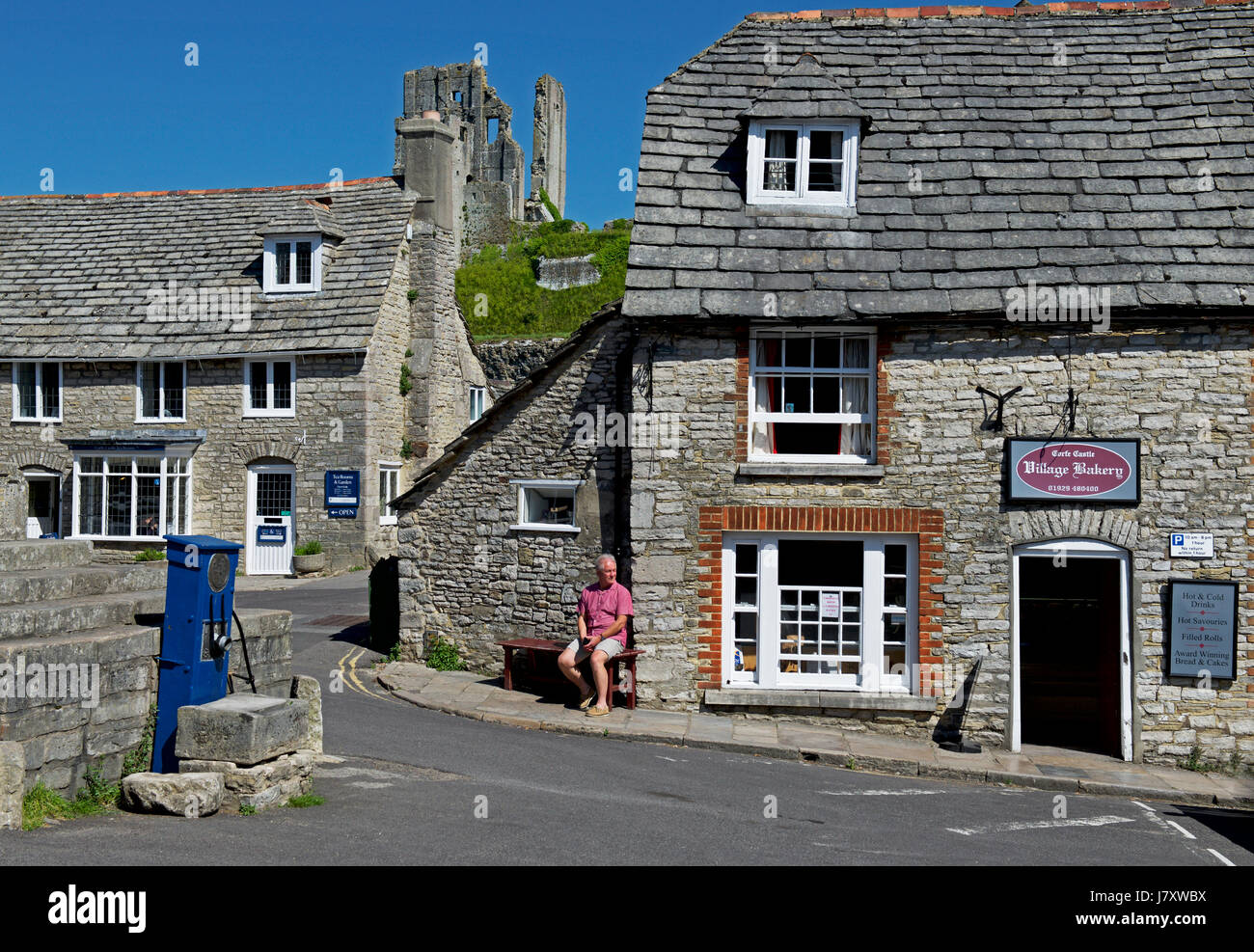 Man relaxing on bench in the village of Corfe Castle, Dorset, England UK - Stock Image