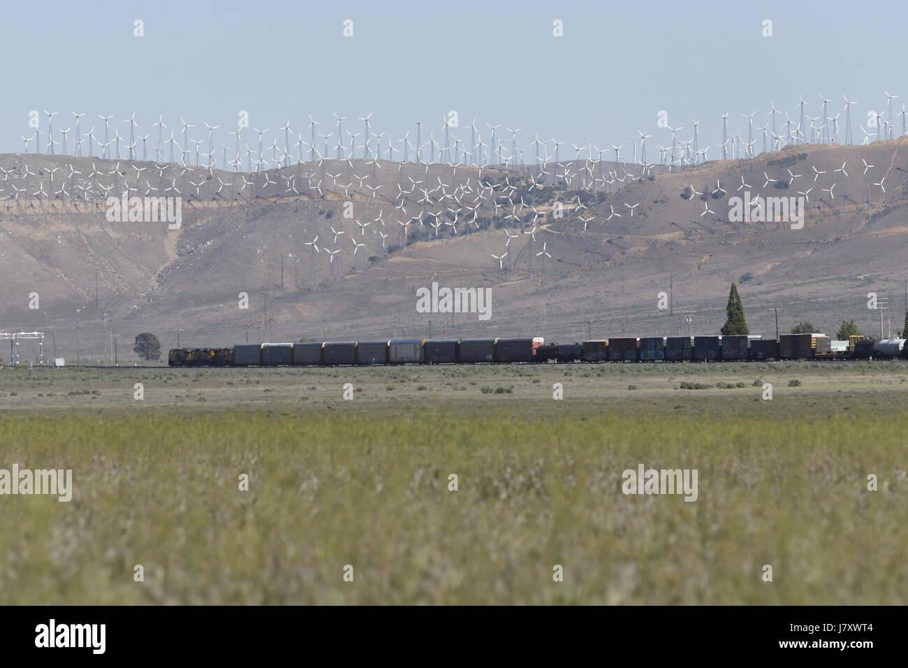 Tehachapi, CA. April 30, 2017. A cargo train passes beneath windmills in the Tehachapi Wind Resource Area, California's - Stock Image