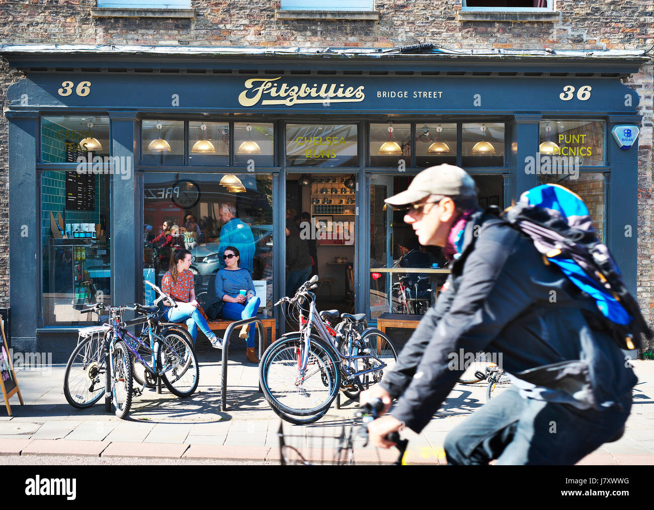 Sunday lifestyle in Cambridge, UK. Cyclist rides past a Cambridge institution of Fitzbilllies cafe in city while - Stock Image